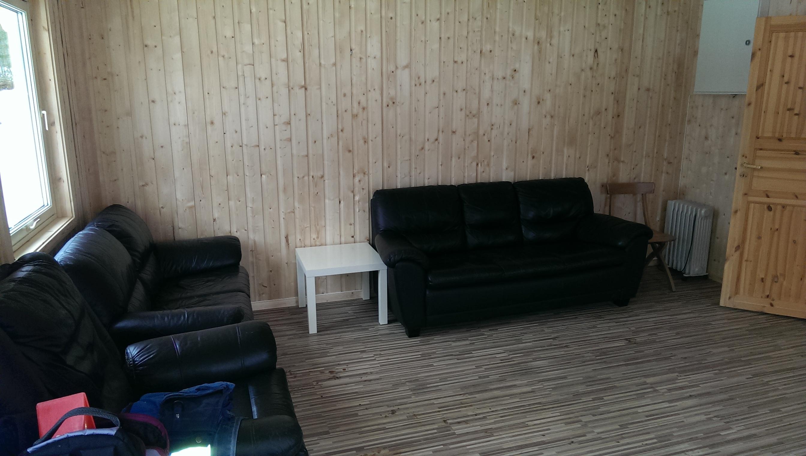 Sofa er satt inn midlertidig i kiosken, inntil bord og stoler er på plass. Legg merke til parkettgulvet :-)